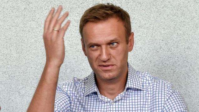 Alexeï Navalny, faisant dos à un mur, a la main droite levée à la hauteur de son visage.