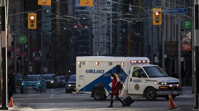 Une ambulance roule dans les rues de Toronto pendant qu'une piétonne portant un masque traverse la rue.