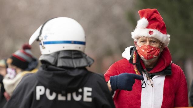 Un policier se tient devant un homme habillé en rouge aux couleurs du père Noël.