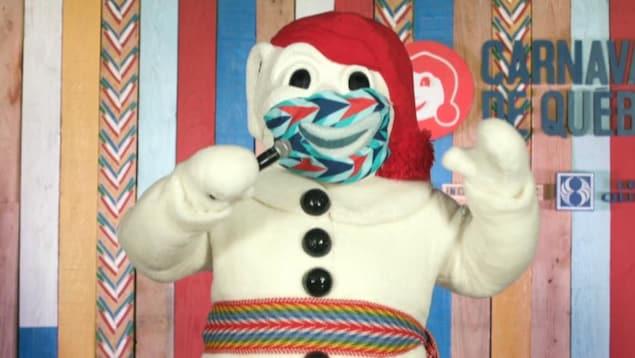 Le Bonhomme Carnaval sur une scène, il porte un masque et parle avec un micro.