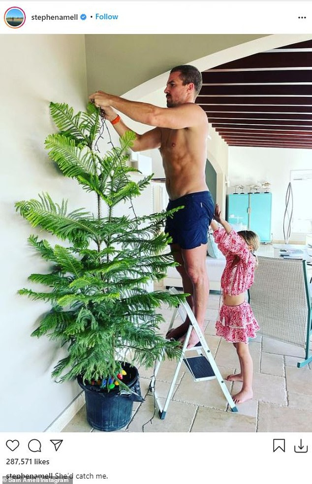 Sweet snap: Stephen Amel shows off his toned physique while hanging lights on a tree, while his daughter Mavi tries to grab him up a flight of stairs