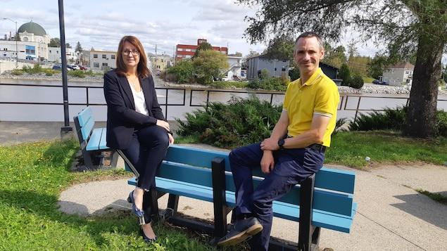 Une femme et un homme sont assis sur un banc à l'extérieur. Au loin on reconnaît la cathédrale d'Amos.