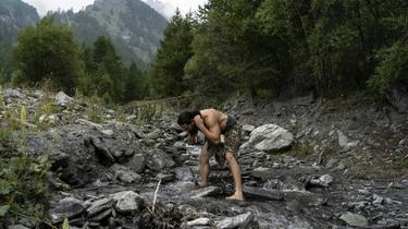 A man dressed as a Neanderthal man washes in a river in the Italian Alps [MARCO BERTORELLO / AFP/Archives]
