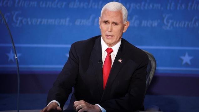 Mike Pence parle assis derrière un bureau lors d'un débat.