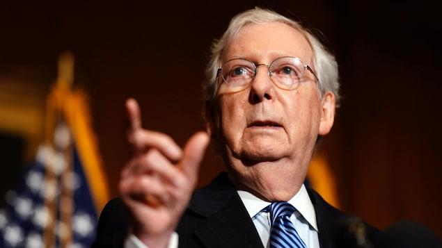 Mitch McConnell, devant un drapeau américain, le doigt levé vers quelqu'un.