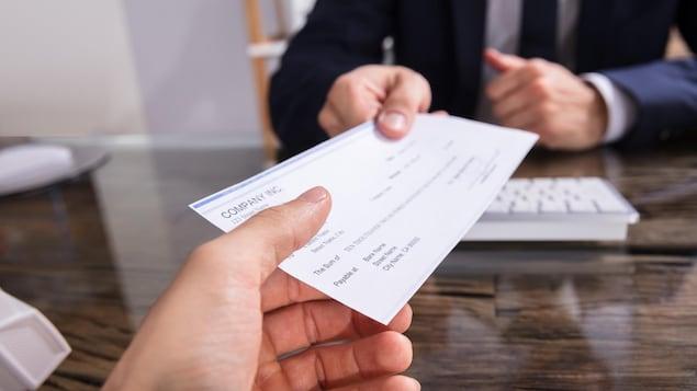 Une personne remet un chèque à une autre personne.
