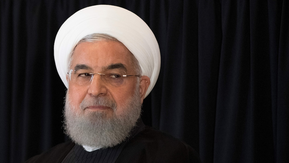 The man with the mid-length beard wears glasses and a head covering, indicating his place in the Iranian hierarchy.