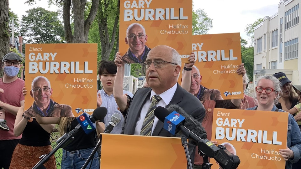 Gary Burrill speaks from the podium surrounding people holding election posters.