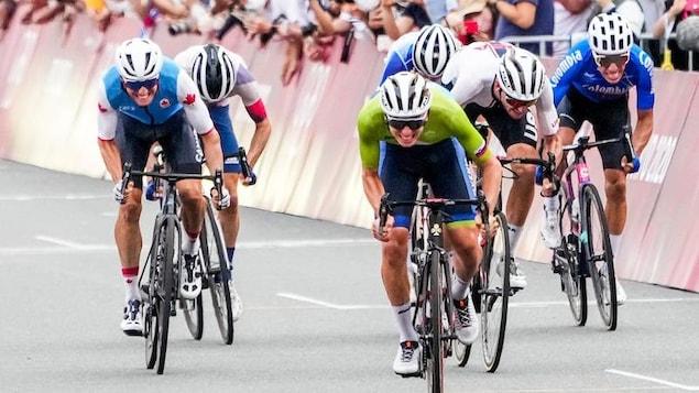 Un cycliste célèbre sa victoire après avoir traversé le fil d'arrivée