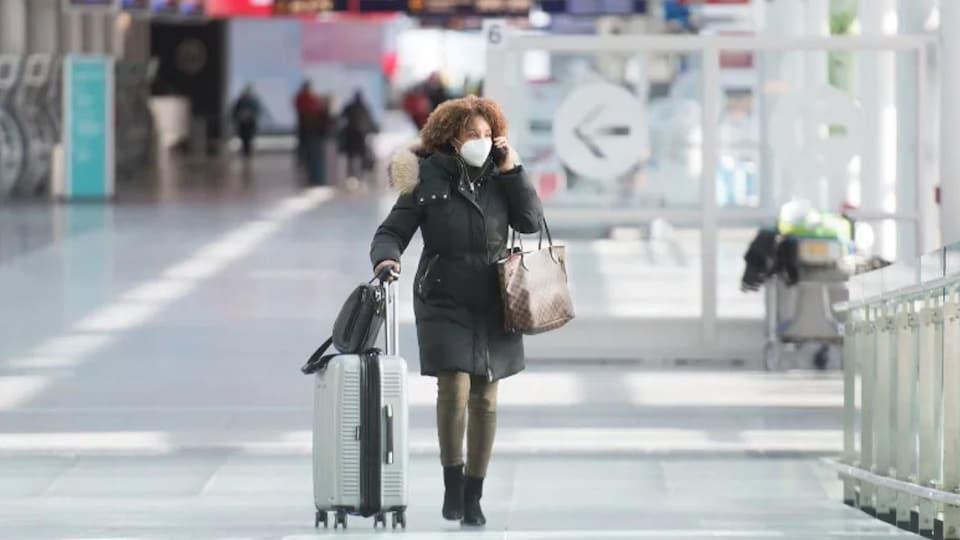 A passenger wears a face mask as he passes through Montreal-Trudeau International Airport.
