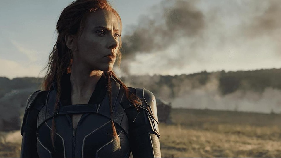 A woman dressed as a superhero looks at the horizon.  Black smoke appears in the background.