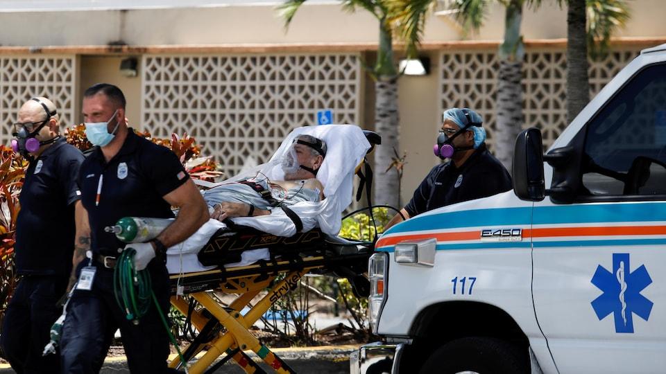 Three paramedics pushed a man lying on a stretcher.