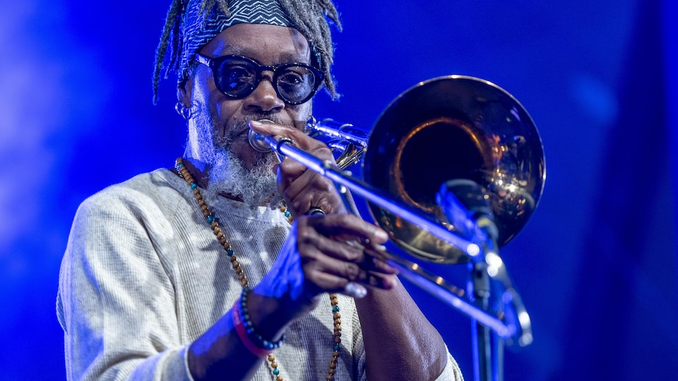 A musician plays the trumpet on stage.