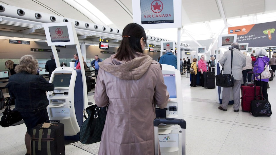 Passengers check in at the kiosk.