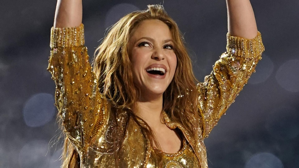 Shakira smiles and throws her hands in the air.