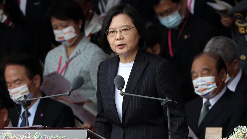 A woman makes a speech at the podium.